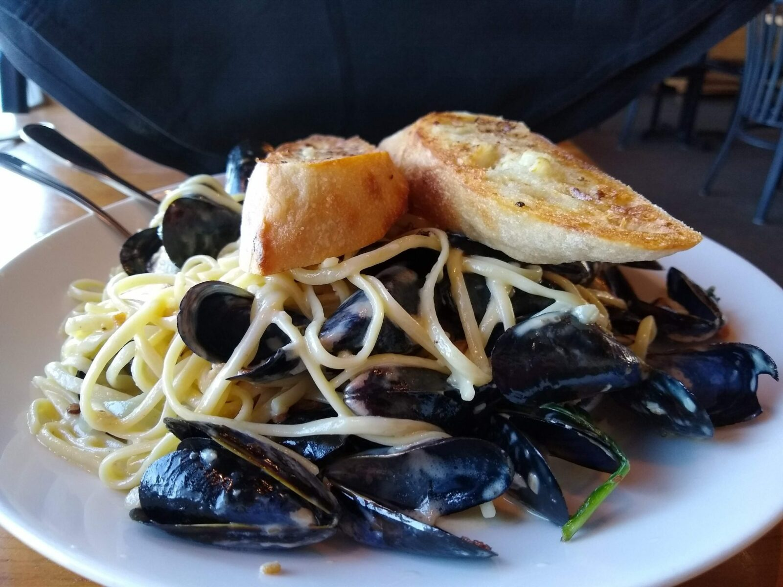 A plate of Penn Cove mussels with pasta and bread on top