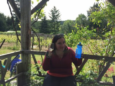 A women in biking clothes is smiling and holding up a waterbottle and a wine glass with a small amount of wine in it. She is sitting by a wooden railing and there is a vineyard in the background