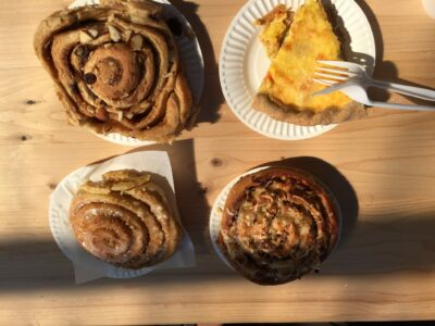 Three cinnamon rolls and a slice of quiche on paper plates on a wooden table