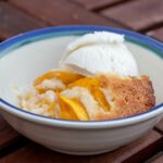 A white bowl with a blue rim contains a piece of peach cobbler and a scoop of vanilla ice cream