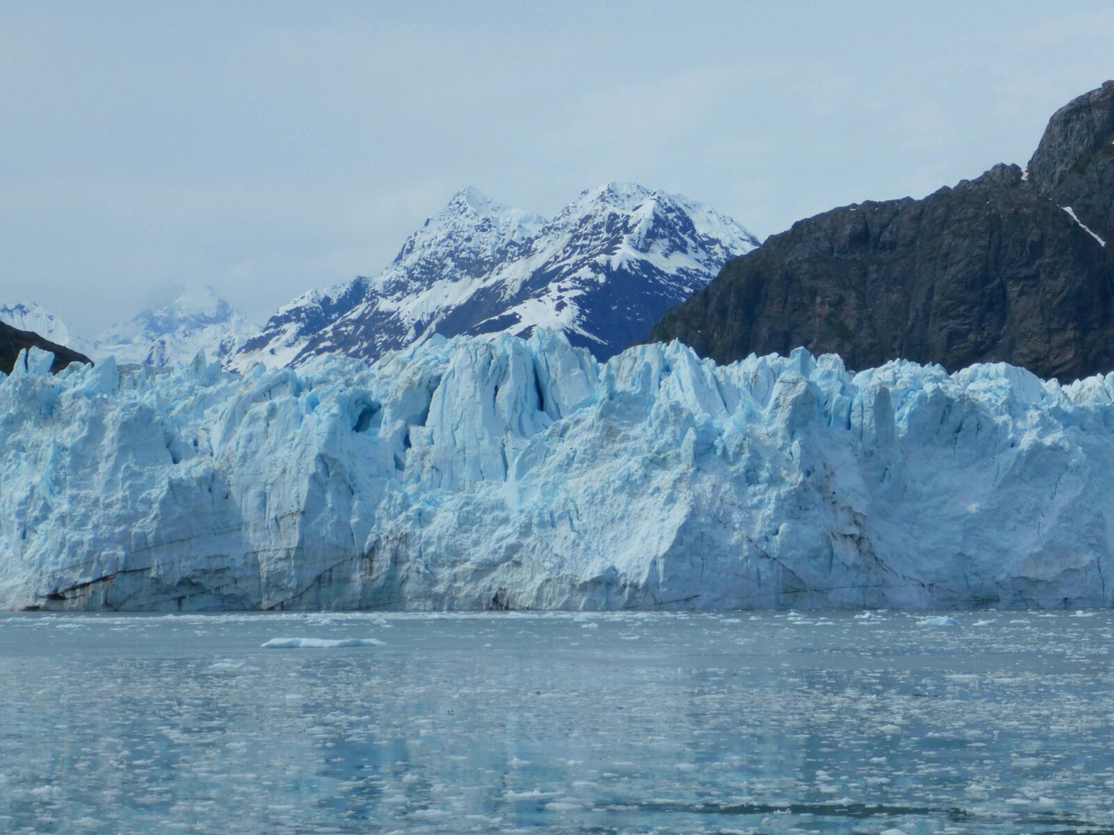 A glacier of blue ice at the ocean with lots of small icebergs floating in the water. There are tall snow covered mountains in the background