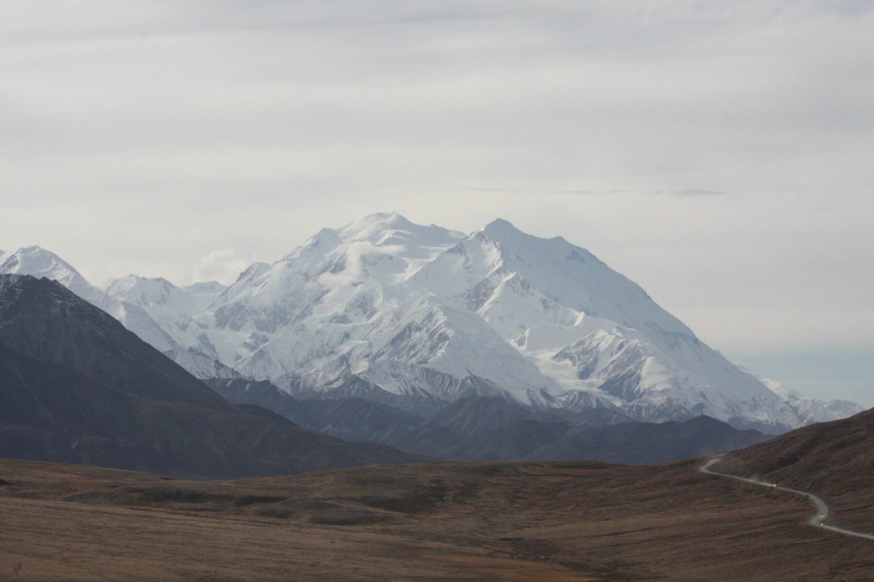 Denali, the High One, is seen across a valley in Denali National Park. There is a road following the valley