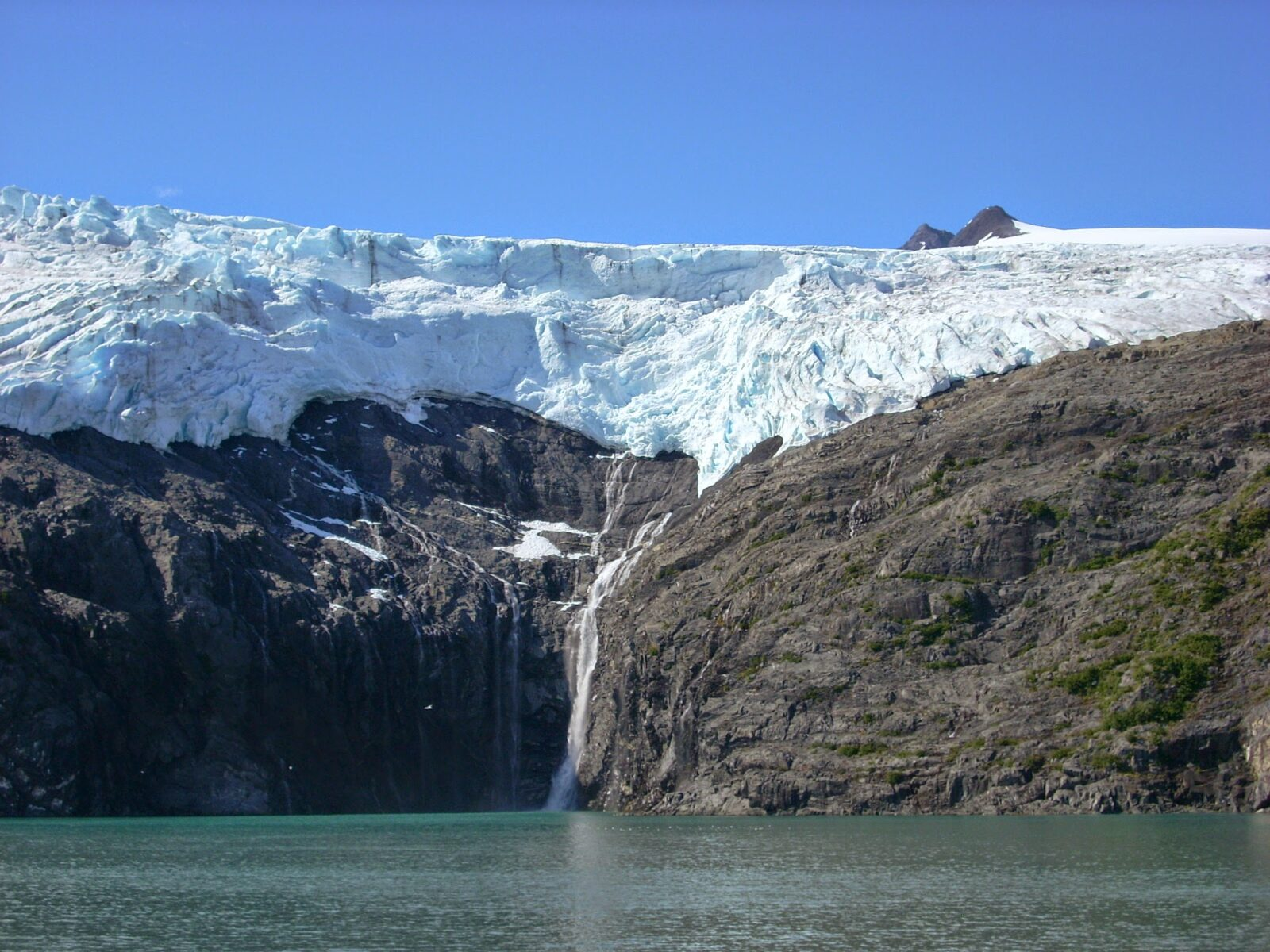 A hanging glacier over rocks next to the water with a small waterfall coming down on a glacier cruise, one of the best day trip tours in Alaska