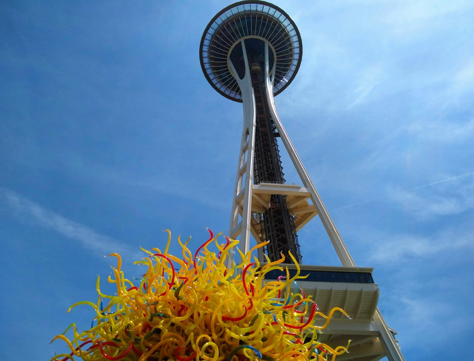 The Space Needle against the blue sky with a yellow glass sculpture in the foreground.