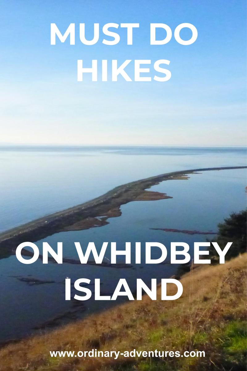 A sand spit on a beach extends away from a grassy hillside encircling a lagoon. Beyond there is water in the distance on a sunny day. Text reads: must do hikes on whidbey island