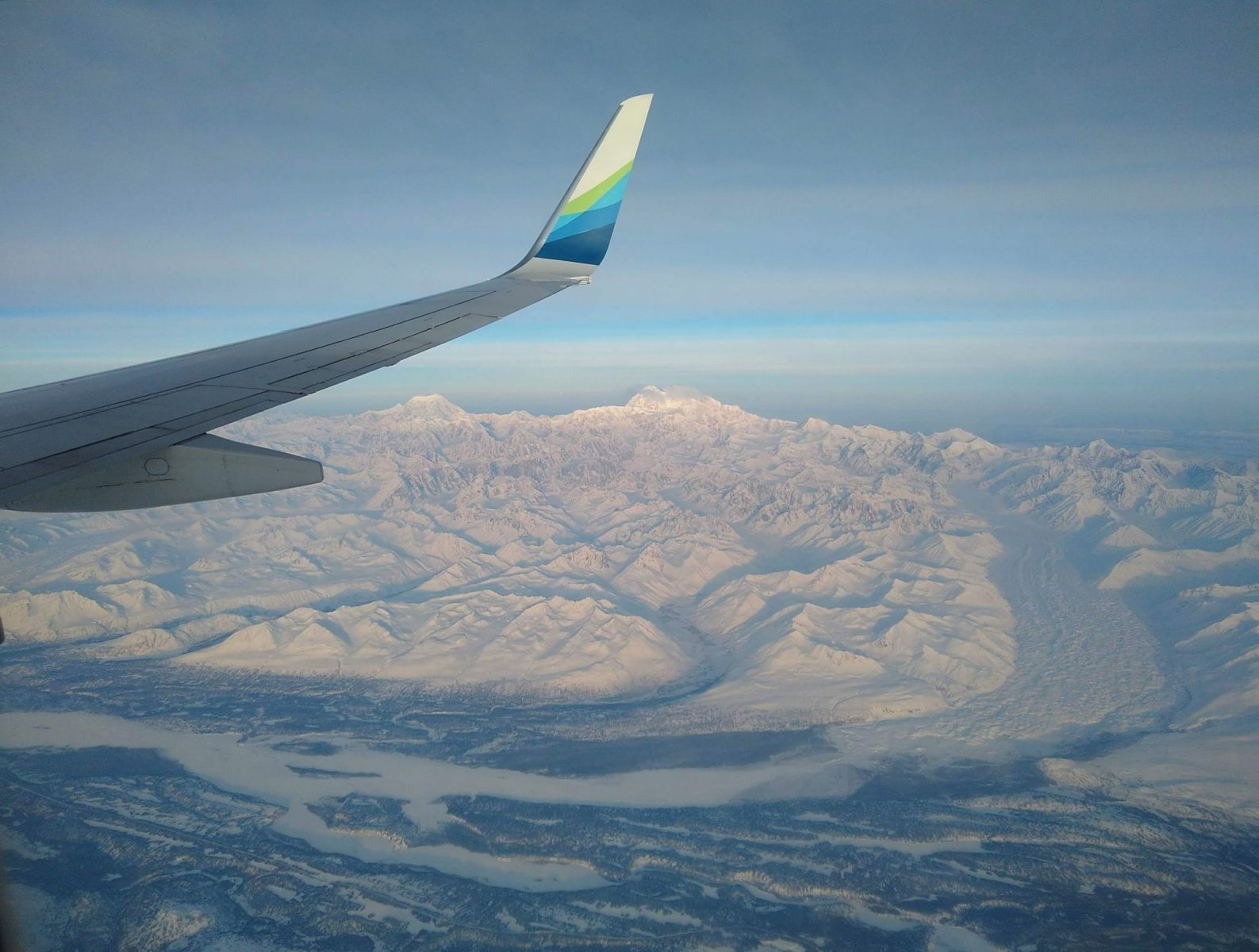 an airplane wing over high mountains and glaciers and a river below