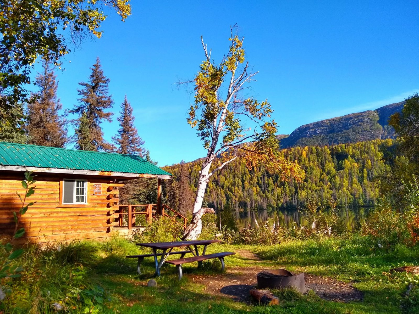 the side of a wooden cabin next to a lake with forest around it. There is a picnic table and a fire pit in the foreground. A cabin rental is a great way to camp without having to fly with camping gear