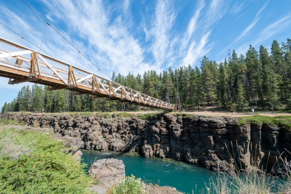 A pedestrian wood and metal bridge crossing a turquoise river in a rocky canyon. There are trees next to the canyon