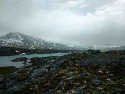 Mountains have lingering snow across a rocky pass with a small lake. There are thick clouds above