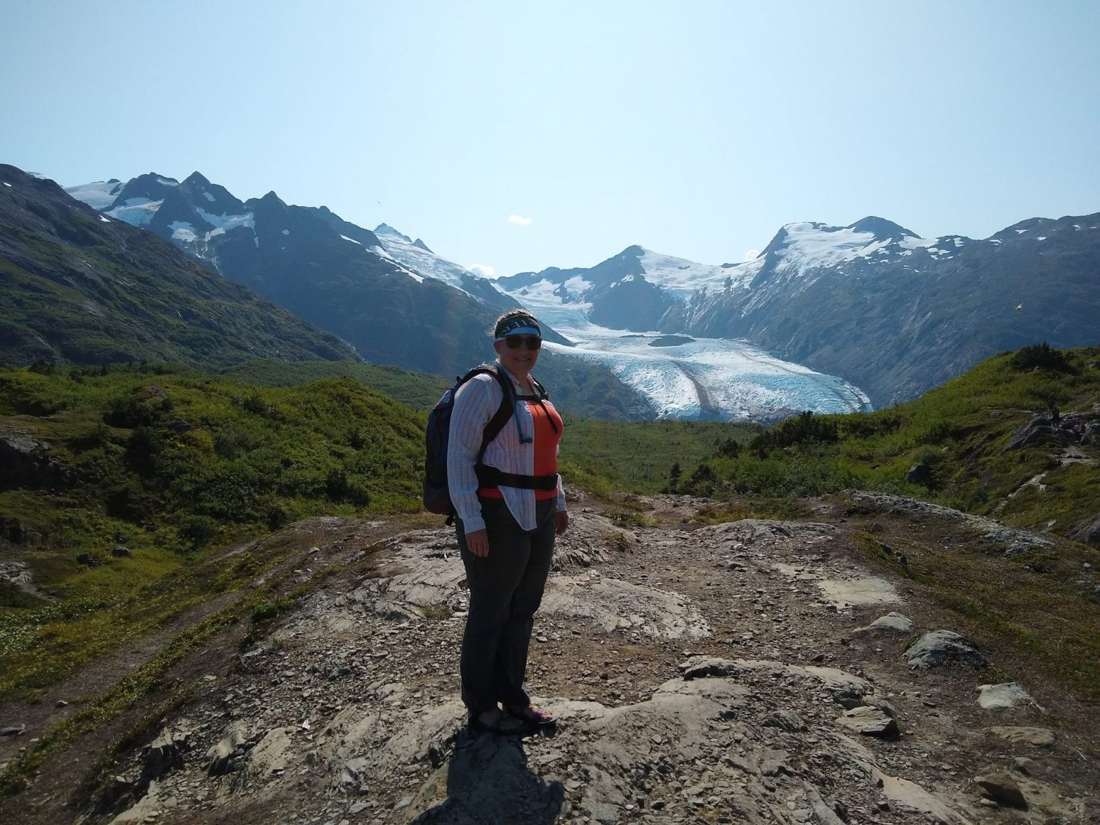 A hiker on a rocky overlook near a glacier. The hiker is wearing a lightweight button up shirt over a tank top and hiking pants and a backpack and sunglasses