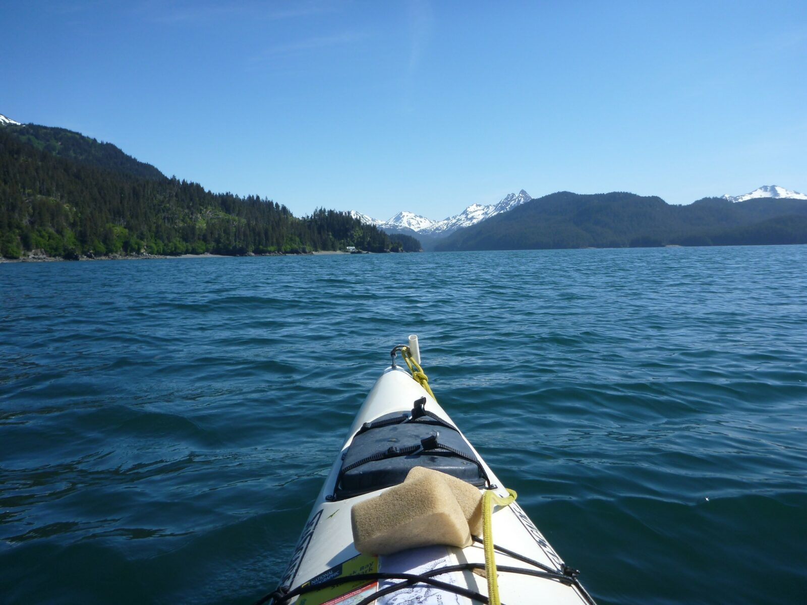 The front of a white kayak from the perspective of the person paddling it. In the distance are high snow capped mountains and evergreen forested hillsides