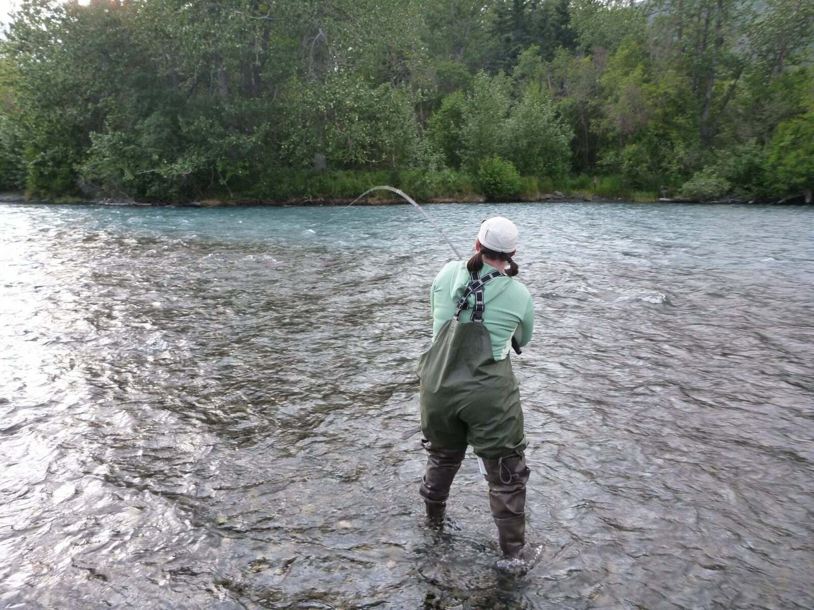 A woman fishing in a river with a hat, waterproof green overalls and brown hip waders