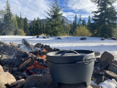 A dutch oven sitting next to a campfire. It's a sunny day and there is a snowy forest around the fire