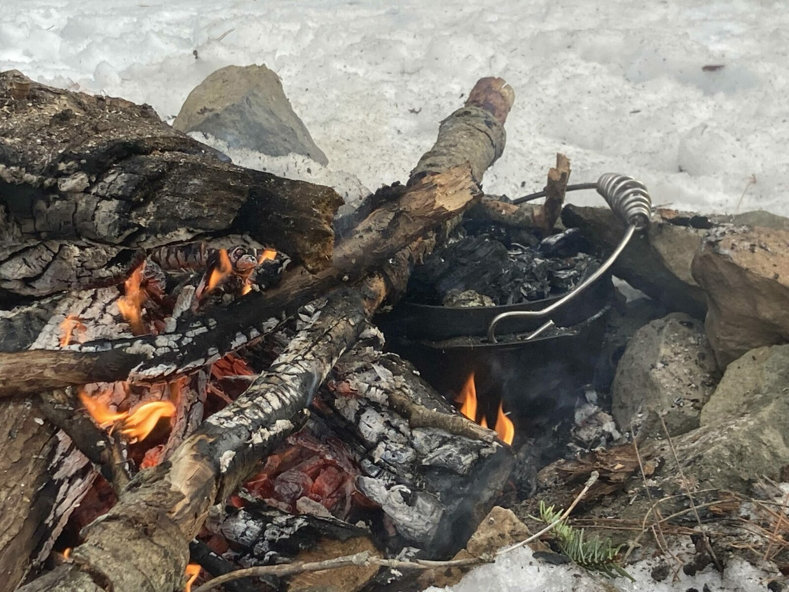 A dutch oven inside a campfire. Some of the coals and logs are on top of it. The campfire is surrounded by snow