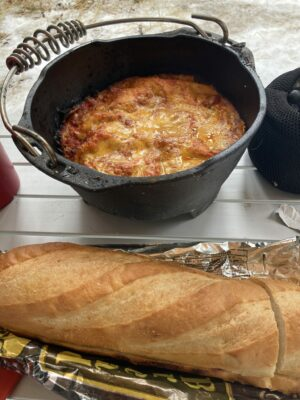 Lasagna in a dutch oven with a loaf of garlic bread sitting next to it on a table