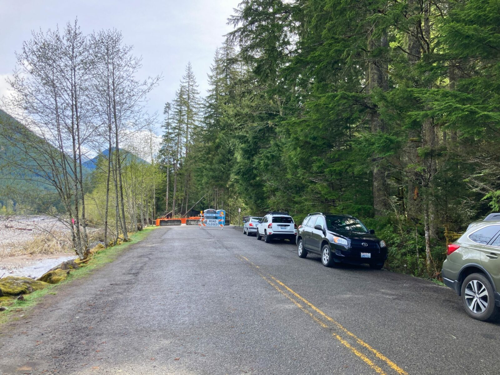 A two lane paved road ends at a barricade with a road closed sign and two port potties. Four cars are parked along the side of the road. There is a forest, hillsides and a river along the side of the road.