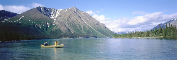 Two people paddle a canoe across a lake on a mostly sunny day. The lake is surrounded by forest and mountains