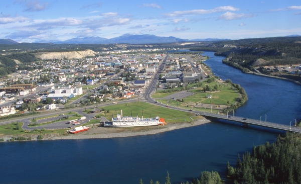 An aerial view of the city of Whitehorse in the Yukon Territory. The blue Yukon River is on the side of town and a bridge crosses it near a historic riverboat. There are hills and mountains in the background