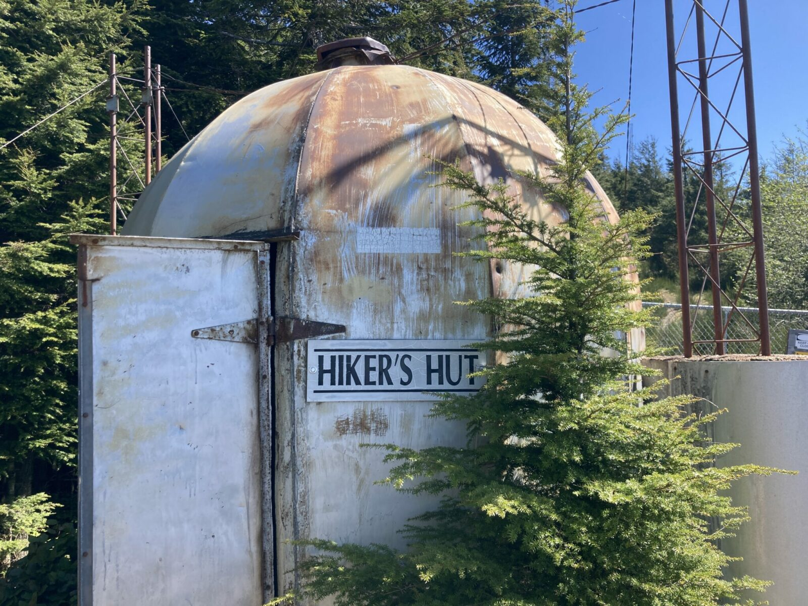 A small white painted metal building with rust on the roof has a sign that says Hiker's Hut and an open door on West Tiger Mountain 1. There is a forest around the hut and some metal poles in the background