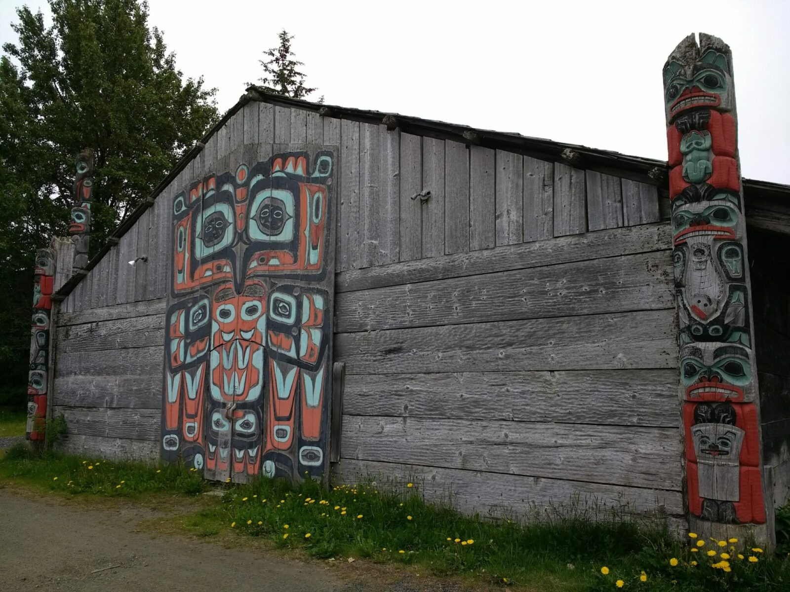A traditional Chilkat tribal house. It is large, one story and made of weathered wood. On the outside is a house screen, a large flat piece of art that goes on a wall. Next to it are two house poles, which are like totem poles but shorter and on the corners of a house. There is also a totem pole behind the house next to a tree