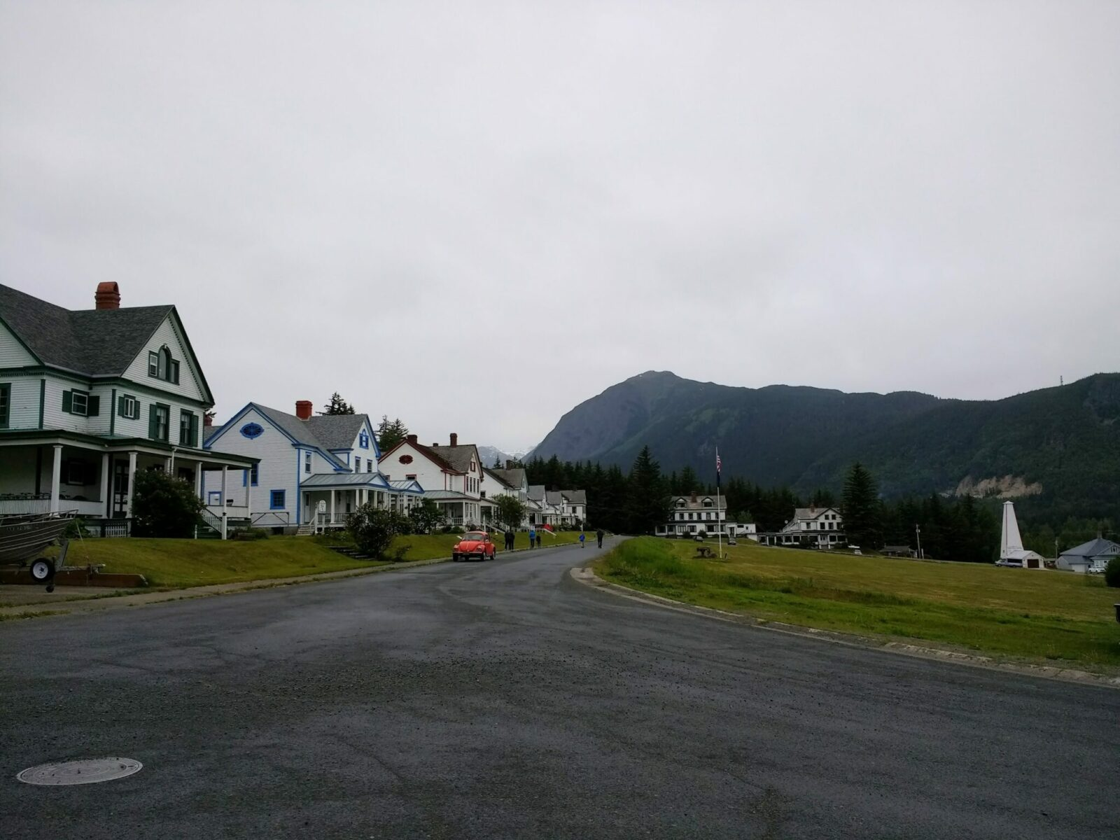 Historic Fort Seward in Haines, Alaska. There is a paved road going by historic army officers housing and a large parade green on the other side of the road. Mountains are in the distance