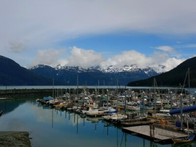 The Haines Alaska small boat harbor with many boats docked inside a breakwater. Across the water are high mountains with snow and some clouds around them on a partly sunny day