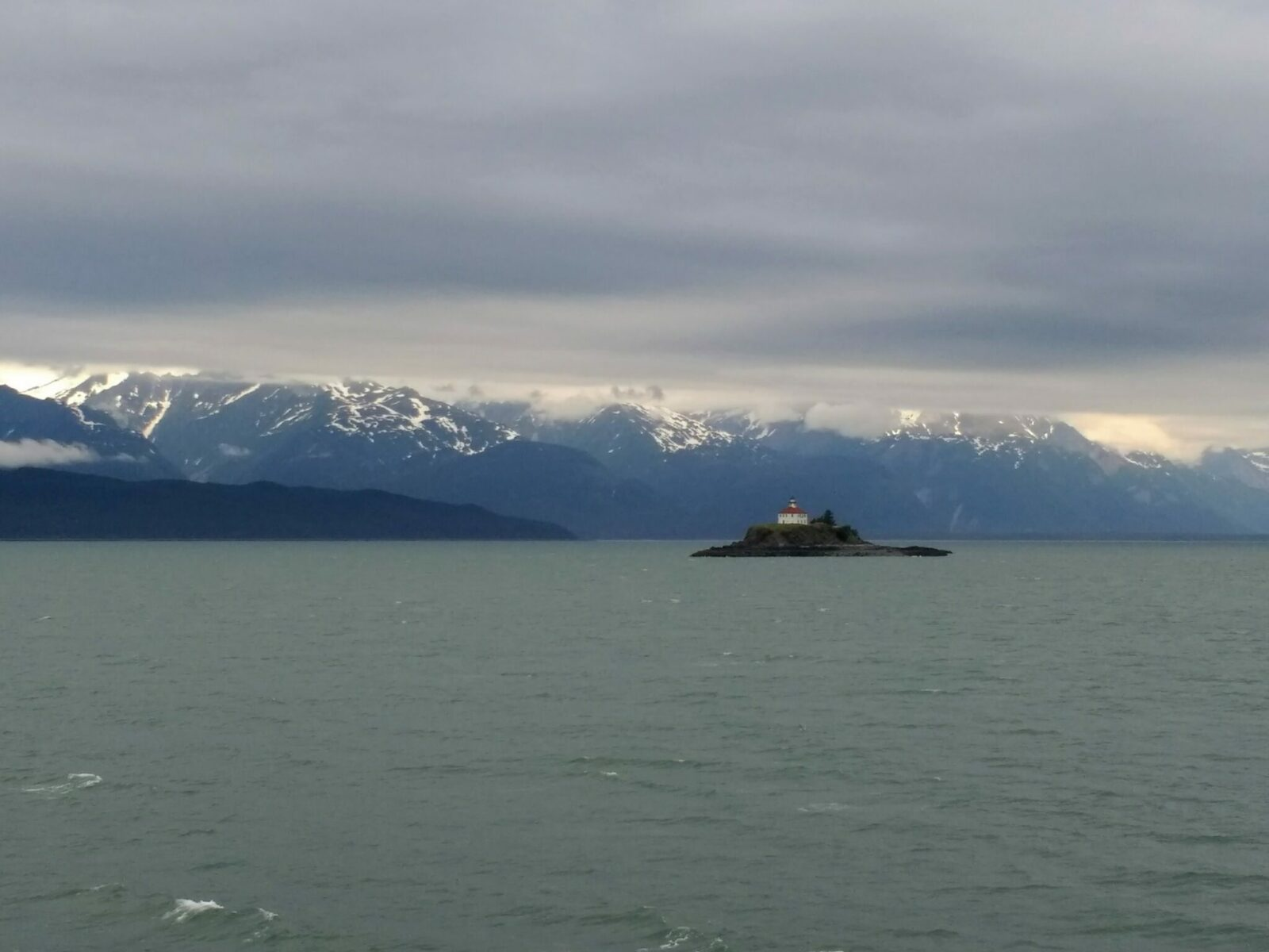 A lighthouse in a white building with a red roof on a small rocky island in the Lynn Canal in Alaska. Around the island is water and forested hills and snow capped mountains on a cloudy day