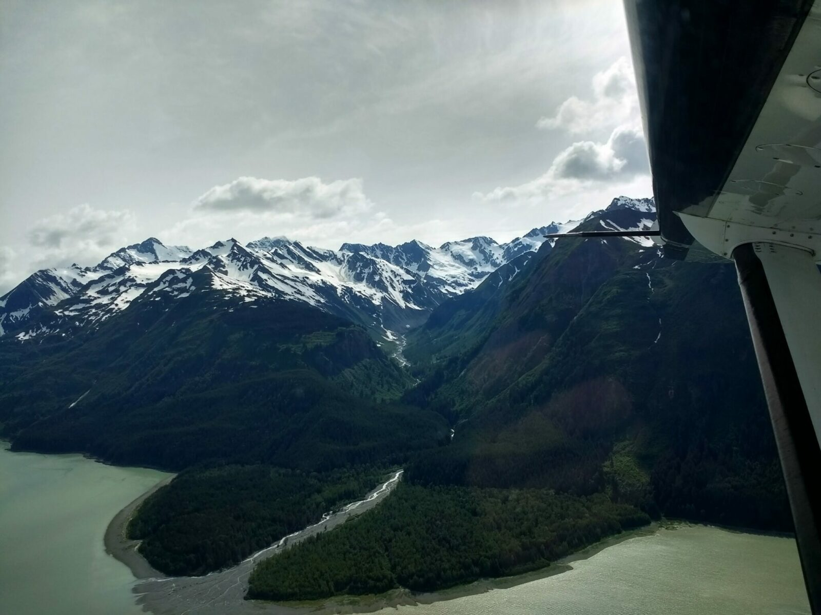 An airplane wing seen from inside a small plane between Haines and Juneau Alaska. Out the window of the plan there is a river coming into the ocean through a forested valley. High snowy mountains and glaciers are above the valley on a partly cloudy day