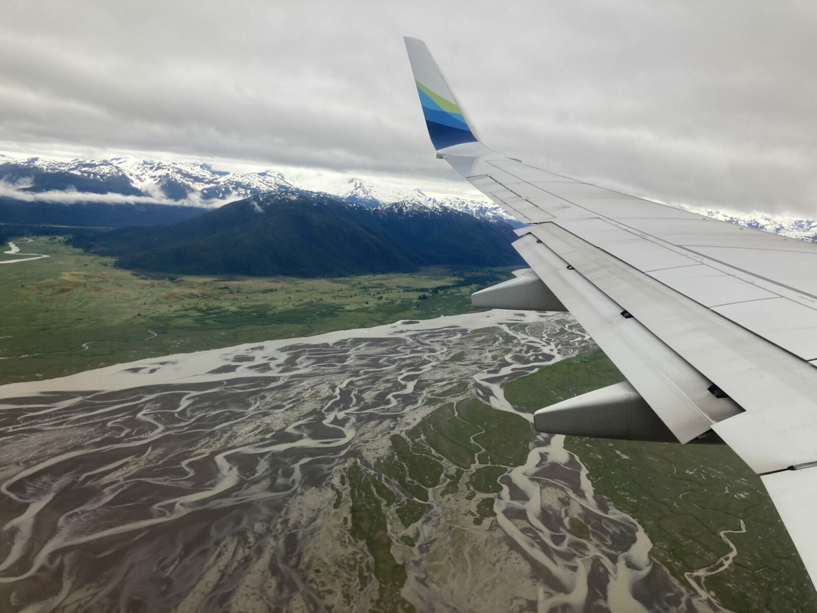 An airplane wing landing in Wrangell Alaska. Below the wing is the sprawling delta of a river surrounded by mountains