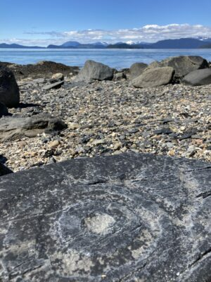 An ancient petroglyph on a dark rock in the foreground. It is a circle with circles around it. It's on a gravel beach with other larger rocks. In the distance are mountains and a few clouds