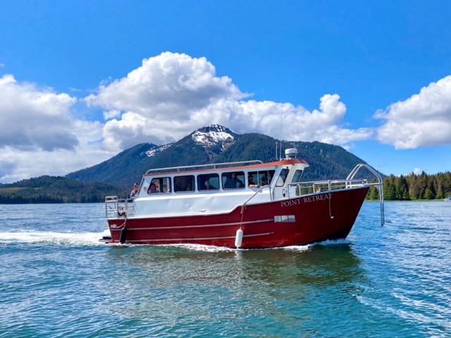 A red and white passenger boat with a cabin with windows and outside decks in the water. In the background are mountains and forests