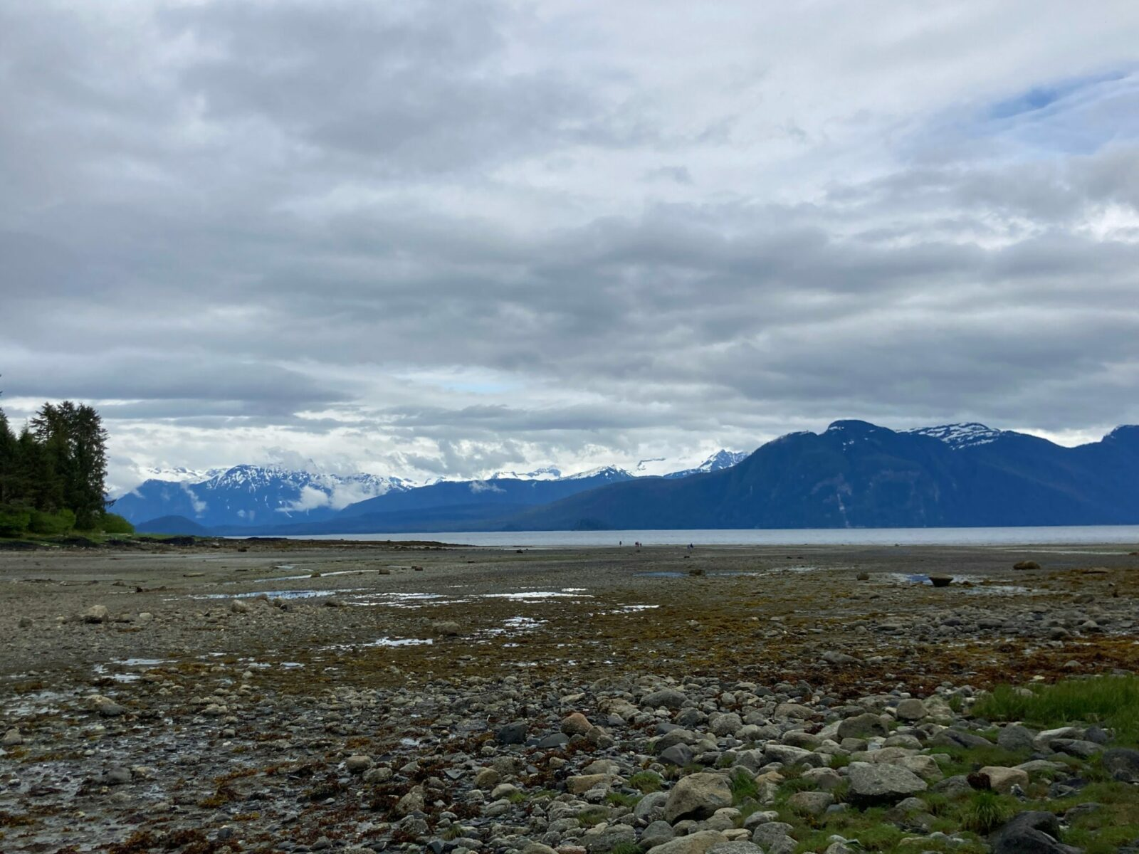 A rocky and sandy beach at low tide with distant mountains on a cloudy day