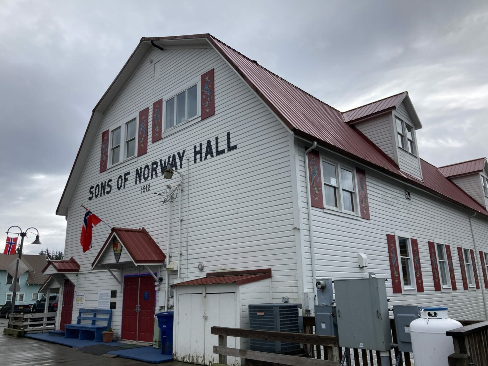 A large barn shaped white wooden building with a red roof. The building says Sons of Norway Hall and has two Norwegian flags