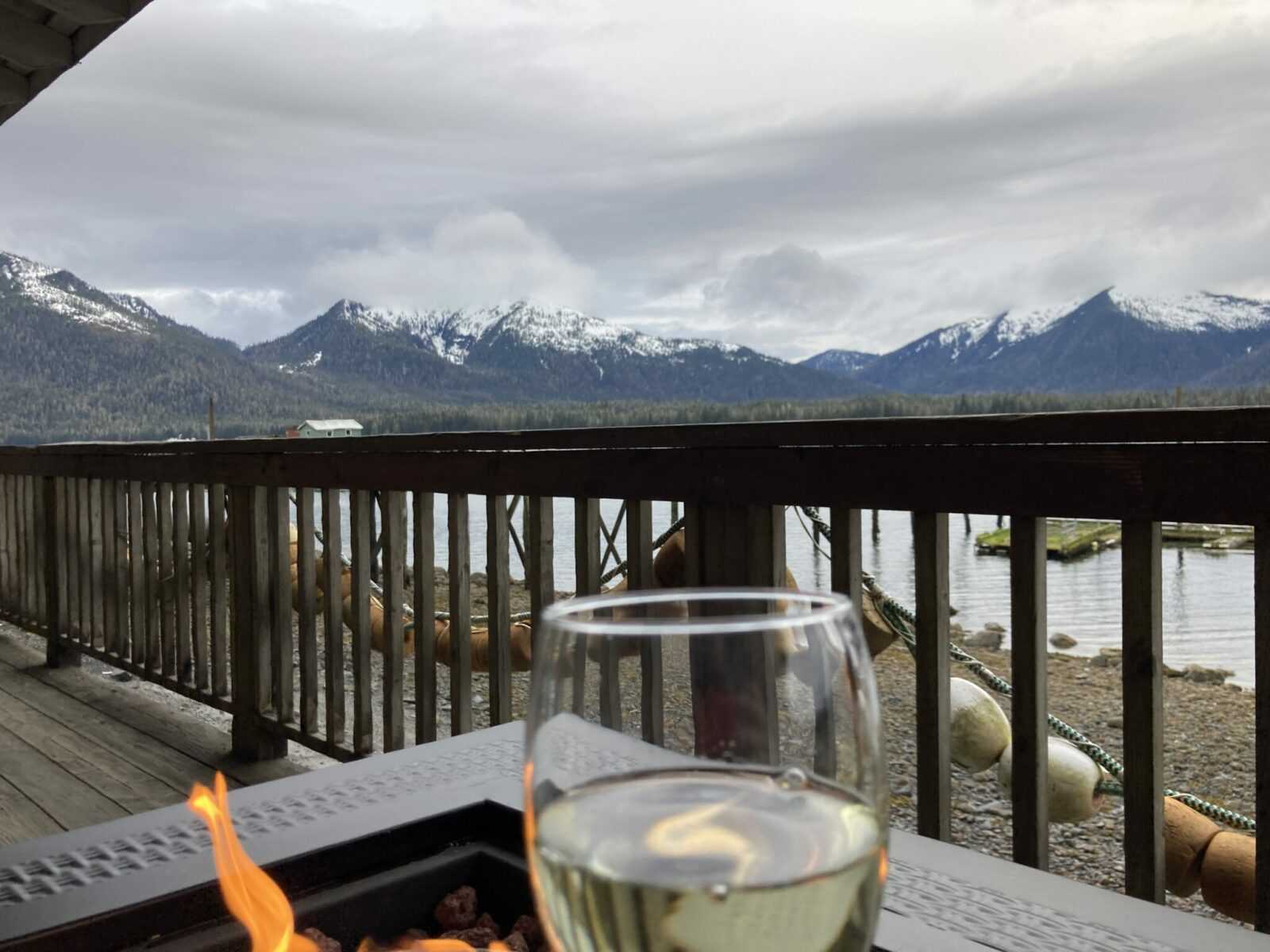 distant mountains with snow and forested lowlands. In the foreground there is a propane firepit on a deck with buoys and a beach at low tide. An out of focus wineglass is in the front