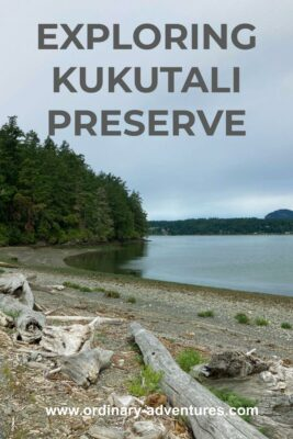 A beach with driftwood and forest alongside. In the distance is other forested land. Text reads: Exploring Kukutali Preserve