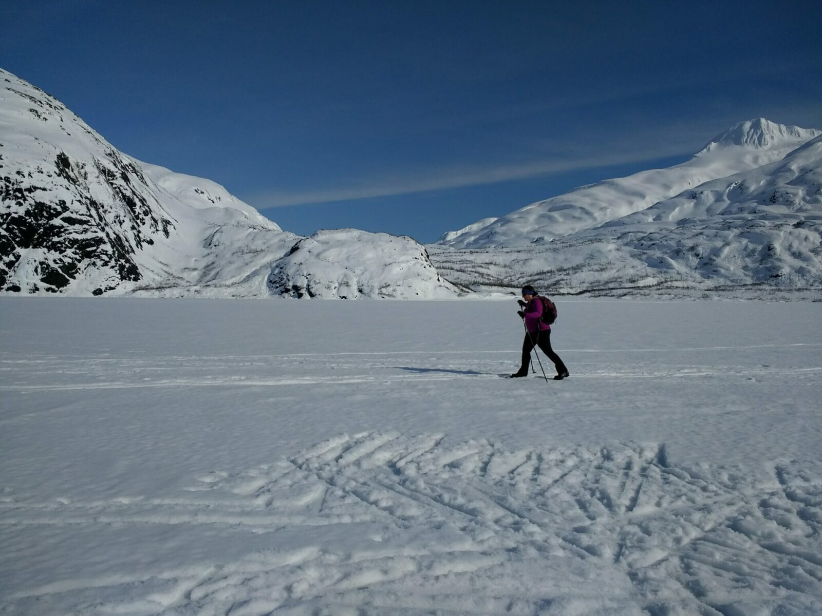 On a weekend trip to Alaska in winter, a cross country skier skies across a frozen lake on a sunny day. There are snowy mountains surrounding the frozen lake