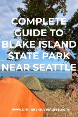 A madrona tree near the beach with water and forested land in the distance. Under the tree are two tents, one orange and one green. Text reads: complete guide to Blake Island State Park near Seattle