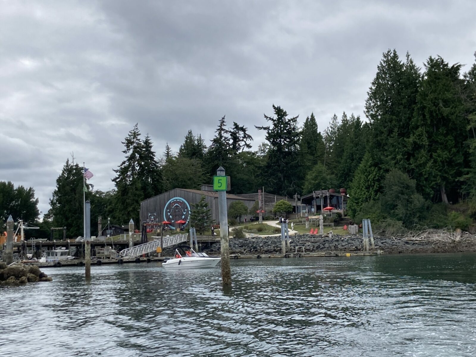 The entrance to a small marina in the forest on Blake Island. There is a building with Northwest Coast art painted on the side facing the marina