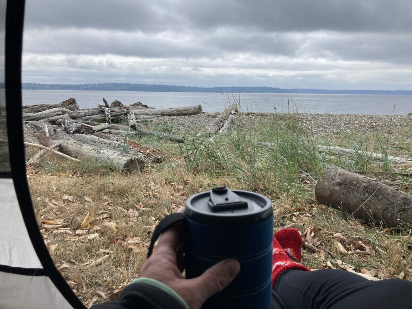 A person sitting in the opening of a tent at the beach. It's a cloudy morning and the person is holding a coffee cup and wearing leggings and red socks. There is distant forested land across the water