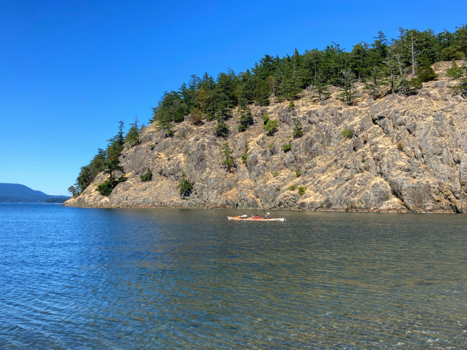Kayaking is a wonderful thing to do on Lopez Island. A trip kayak is in calm water between the beach and a nearby rocky and tree covered island