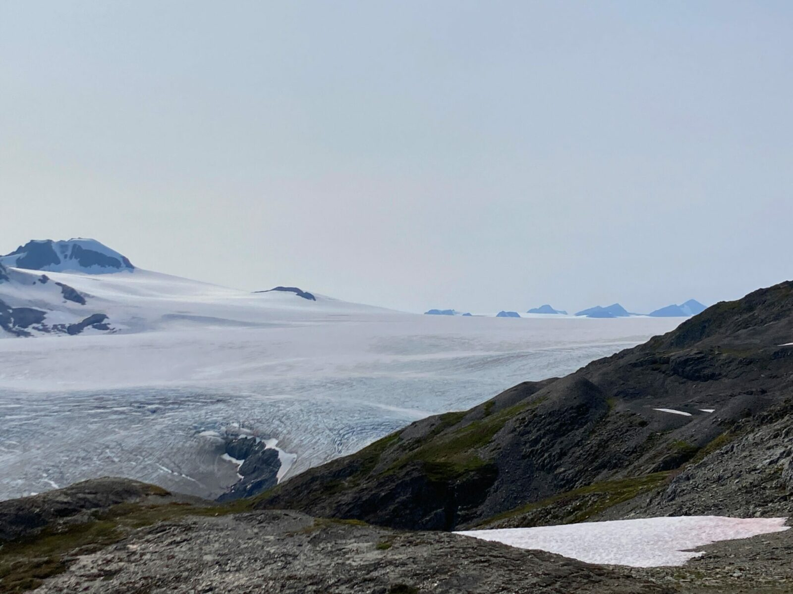 In the foreground are rocky mountains with a glacier next to them. In the distance there are more mountains sticking up from a massive icefield behind the glacier