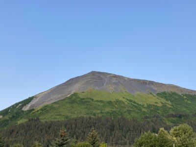 a rocky pointed mountain summit rising up from the forest below. A trail is visible on the side of the mountain.