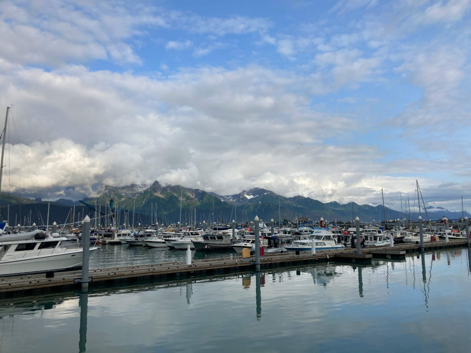 The boat harbor in Seward Alaska. There are many wooden docks with pleasure boats and fishing boats tied up. There are mountains across the fjord from the harbor that are partially obscured by clouds on an otherwise sunny day