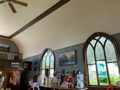 The interior of a former church that is now an art gallery in Seward, Alaska. There are two tall windows with stained glass art and many smaller art pieces on shelves below.
