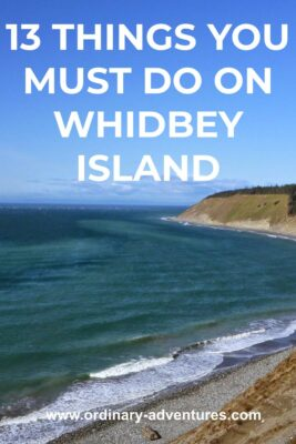Water and a beach at the base of a long bluff on a sunny day. Text reads: 13 things you must do on whidbey island