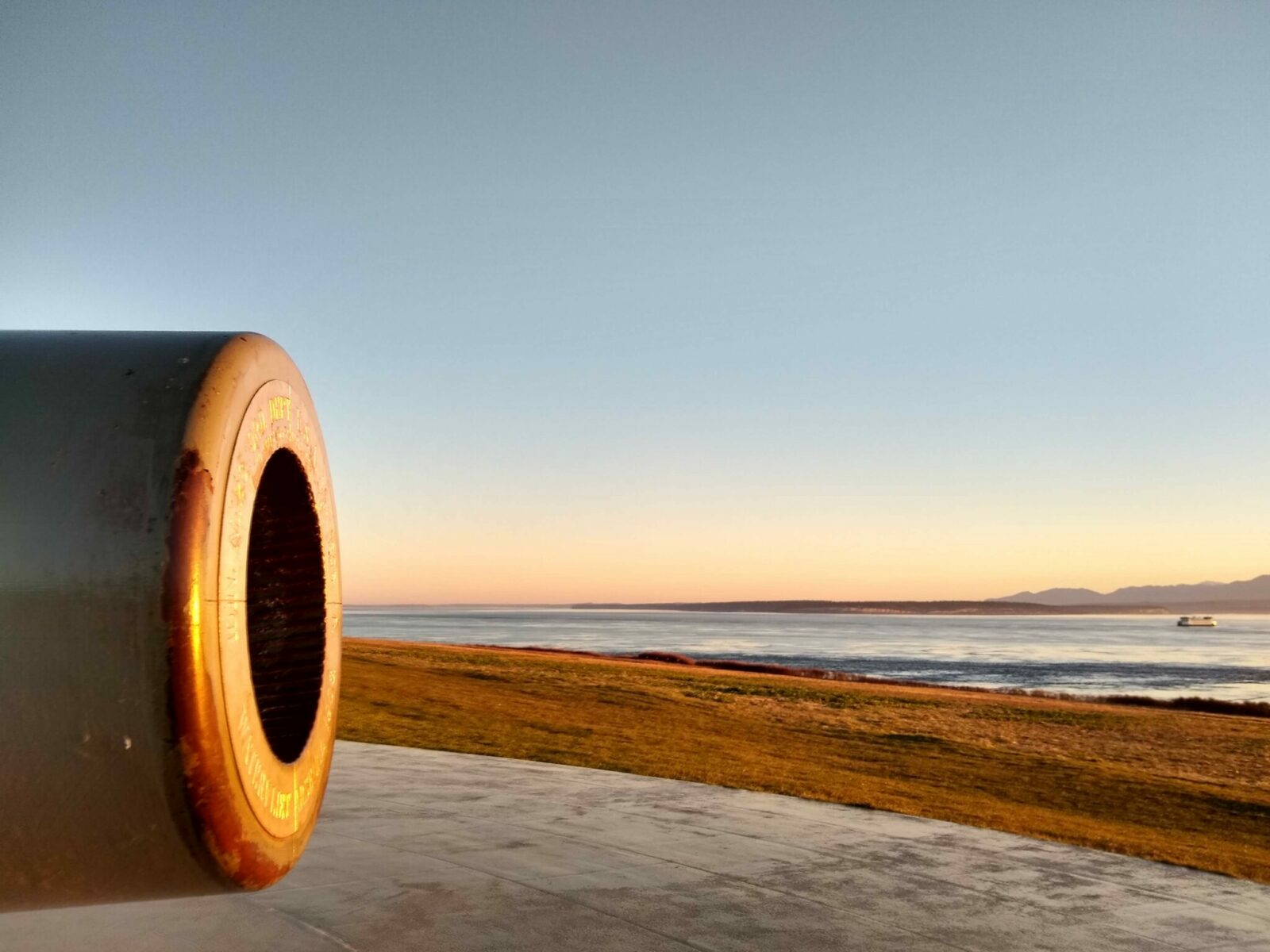 An old cannon at fort casey state park on whidbey island at sunset. There is a field and distant mountains and a ferry in the background