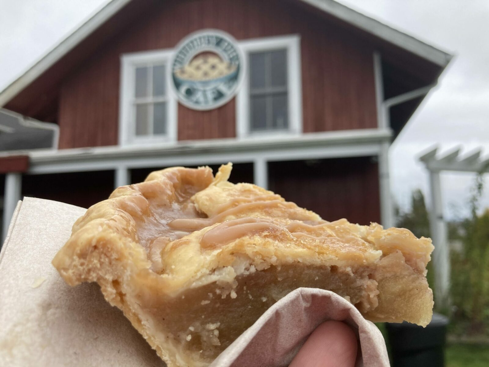 a close up of a slice of pie. A person is holding it in a napkin and there is a blurry barn red building behind