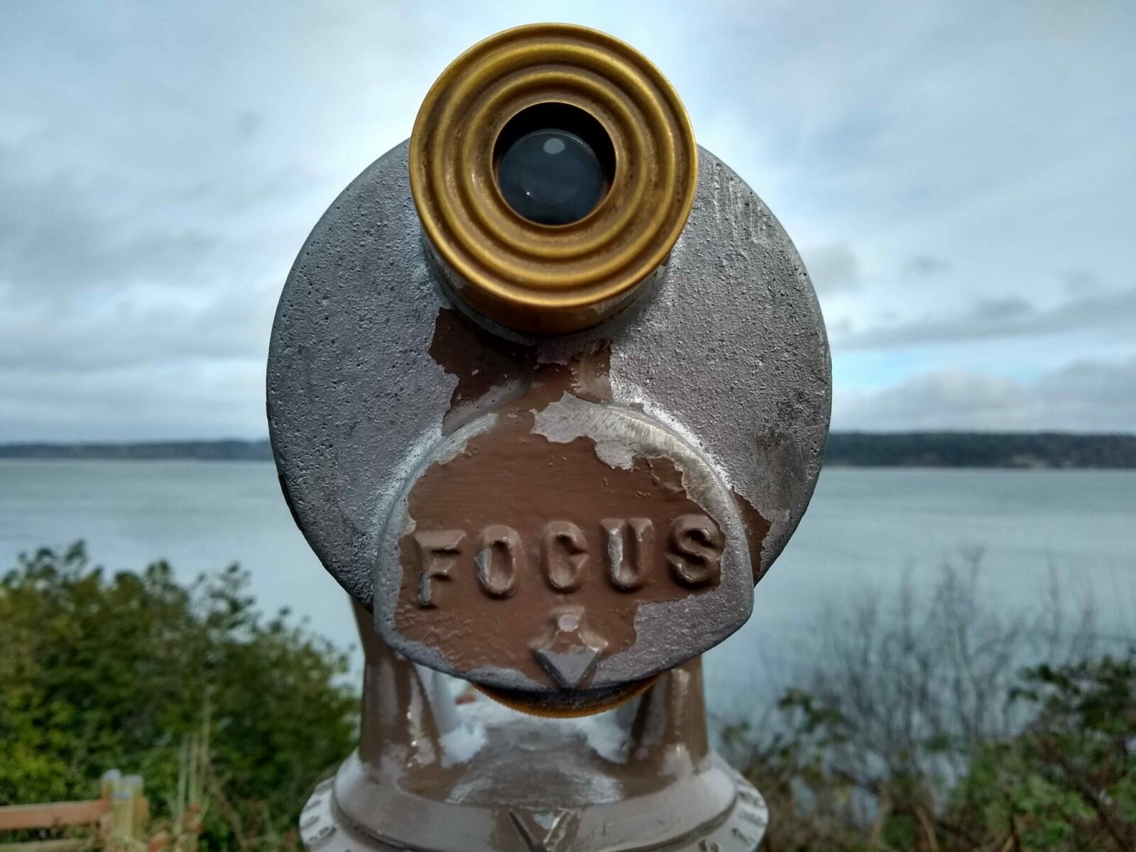 """An old spotting scope that says """"focus"""" near a bluff overlooking the water"""