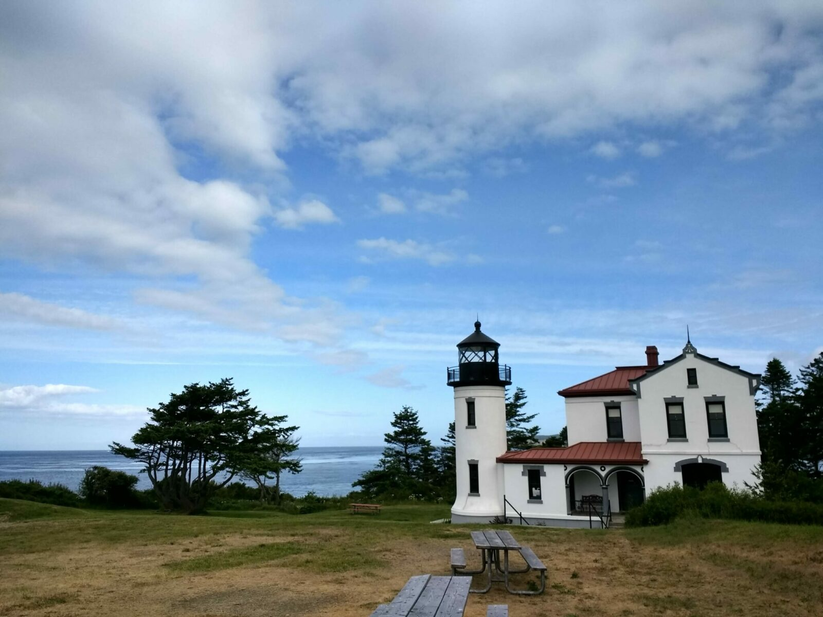 Admiralty head lighthouse on whidbey island. The lighthouse is in a field next to the rocky shore. It is white with a red roof and black trim. The actual light housing is black. There are two picnic tables in the foreground and some evergreen trees around the lighthouse. The partly cloudy sky and ocean are in the background