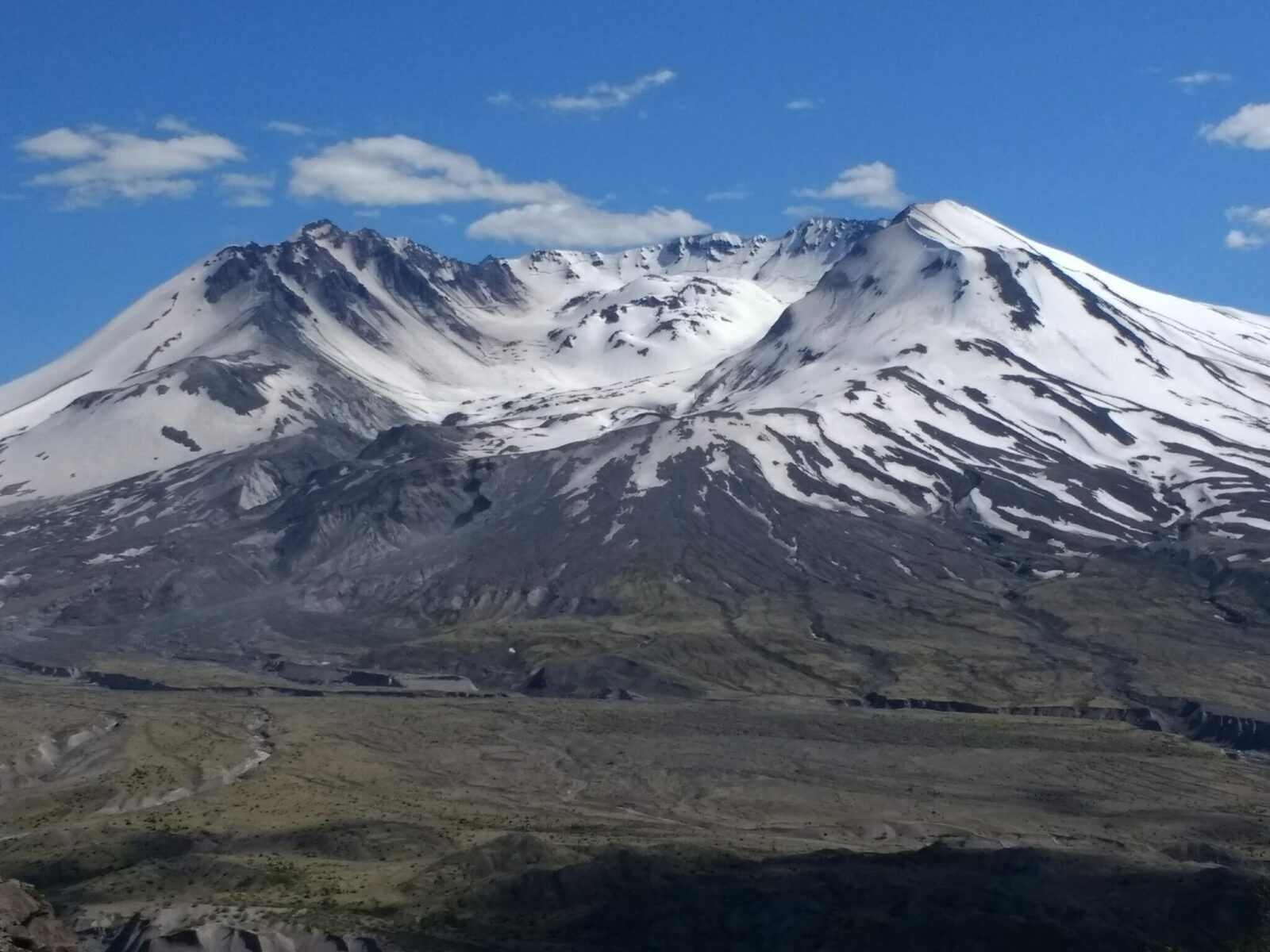 The crater of Mt St Helens with early summer snow still around the summit. In the foreground is the gray and brown landscape of volcanic destruction
